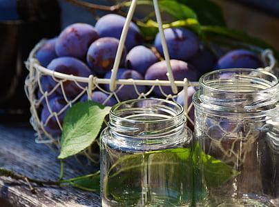bunch of purple fruits near on two glass mason jars