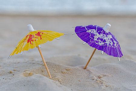 micro photography of two assorted-color mini umbrellas on sand