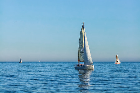 three sail boats on body of water