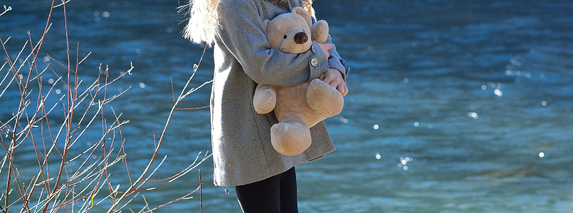 woman holding brown teddy bear near river