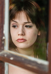woman leans on brown wooden window