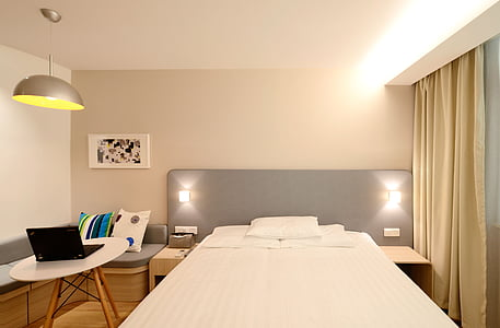 white bedspread near curtain