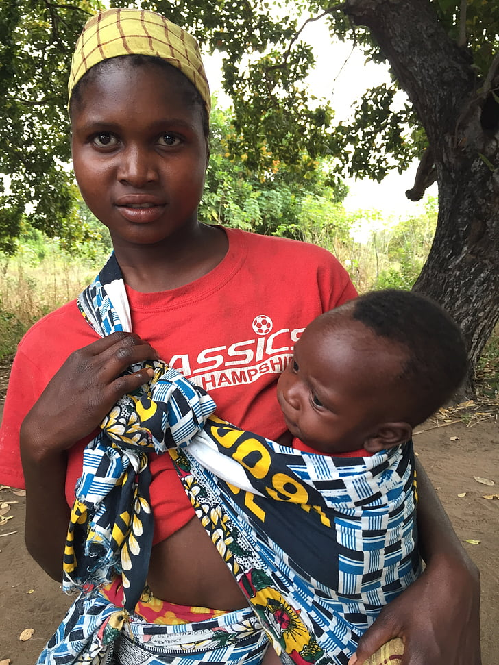 woman carrying baby during daytime