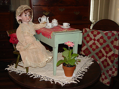 girl doll on brown wooden table