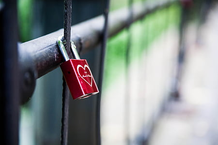 shallow focus of red and silver padlock