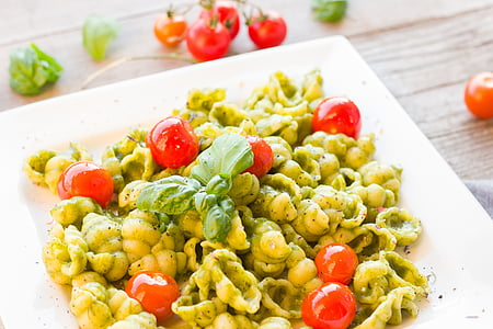 cooked pasta with cherry tomatoes and herb on white ceramic plate