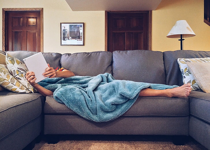 person covered with blue blanket lying on gray sofa