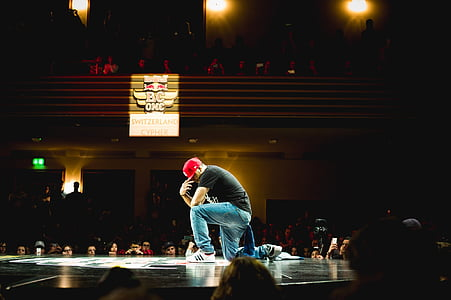 man wearing black t-shirt, red cap and blue denim jeans posing on stage in front of people