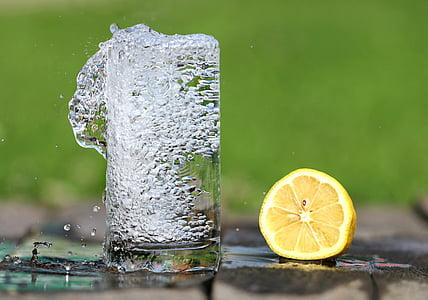 clear drinking glass beside yellow lemon