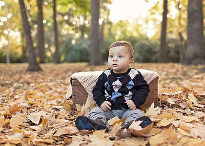 toddler's wearing black sweater outdoor on dried brown maple leaves