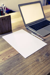 MacBook Air near on blank paper