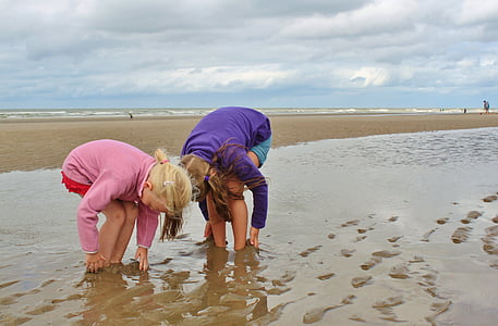 two woman stuck on brown sand beach