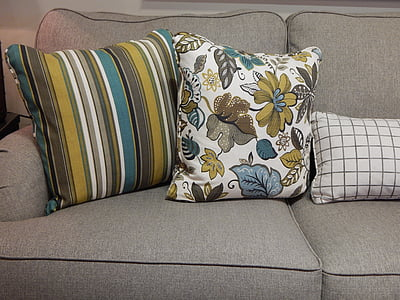 three gray and green throw pillows on sofa