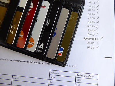 black leather card holder showing assorted cards on receipt paper