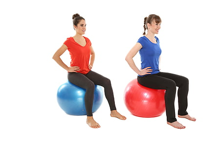 two women sitting on two exercise balls