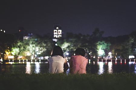two woman seats on green grass at nighttime