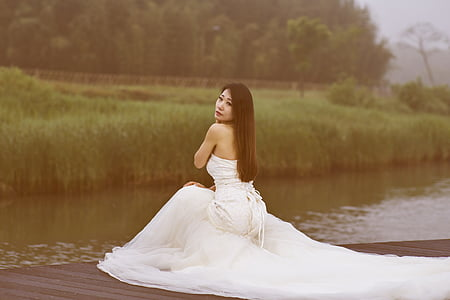 woman wearing white dress kneeling beside lake