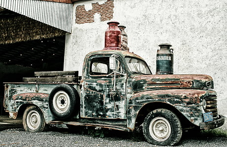 black and brown rusted classic pickup truck park near gray wall with thee assorted-color milk churns on top photo taken during daytime