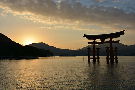 tori gate in body of water during golden hour