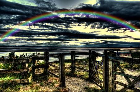 rainbow over horizon during golden hour