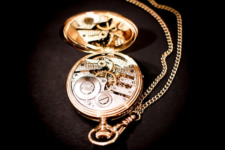 gold-colored skeleton pocket watch