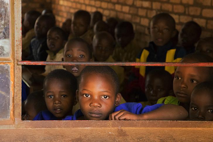 group of kid near brown window