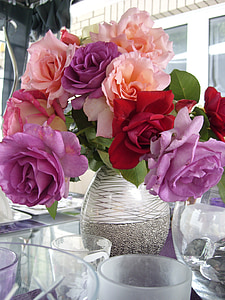 assorted-color rose flowers on gray and white vase