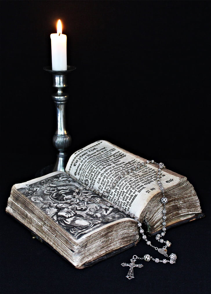 book with gray rosary on top beside silver candle holder