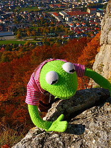 green frog plush toy climbing on brown stone cliff