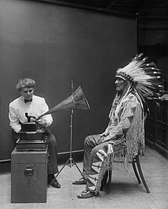 greyscale photo of native American sitting in front of gramophone