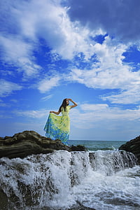 woman standing on rock formation surrounded with water under cumulus cloud