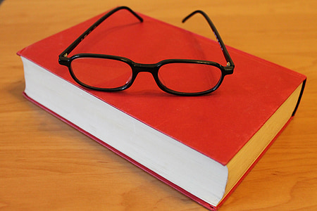 black framed eyeglasses on red closed book