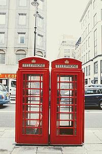 two vintage red telephone booths beside sidewalk