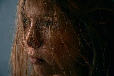 close view of brown-haired woman with messy hair
