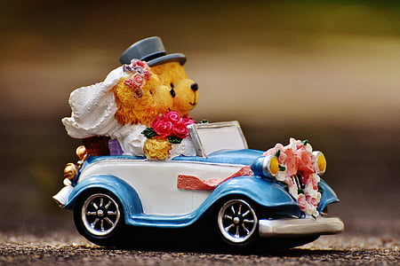 selective focus photography of bride and groom bear riding car figurine