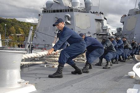 group of men wearing blue uniform pulling white rope