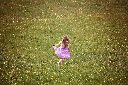 girl in purple dress standing on green grass field
