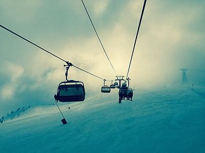 people riding on black ski lift photography