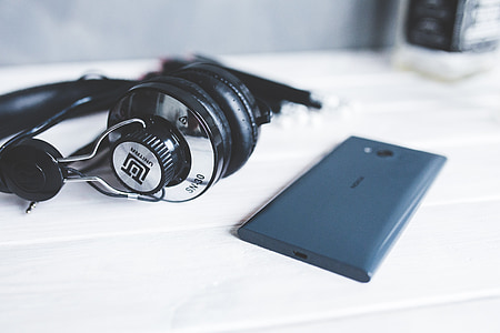 gray and black headphones beside blue Android smartphone