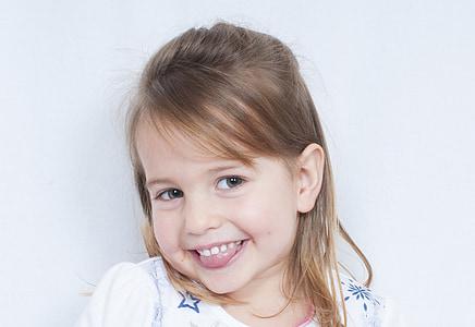 girl wearing white top smiling