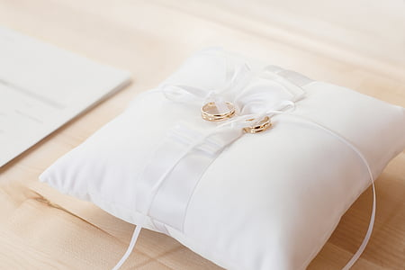 two gold-colored wedding rings on white pillow