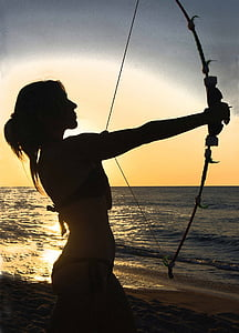silhouette of woman holding compound bow