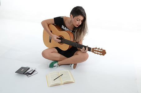 woman playing guitar inside white painted room