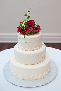 3-tier cake with pink petaled flowers on top