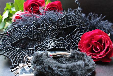 black mask beside red rose