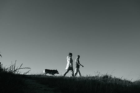 grayscale photography of man and woman walking
