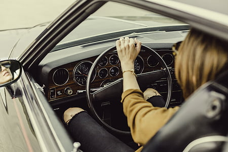 person sits and holds vehicle steering wheel