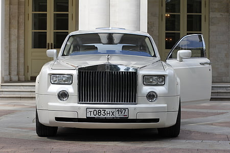 white Rolls Royce Phantom parked near mansion