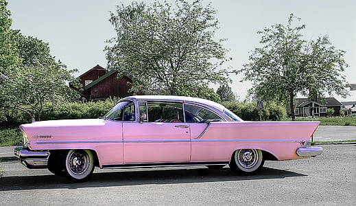 classic pink coupe on road near trees during daytime