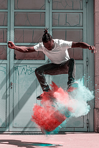 man doing skateboard stunts with blue and orange powder